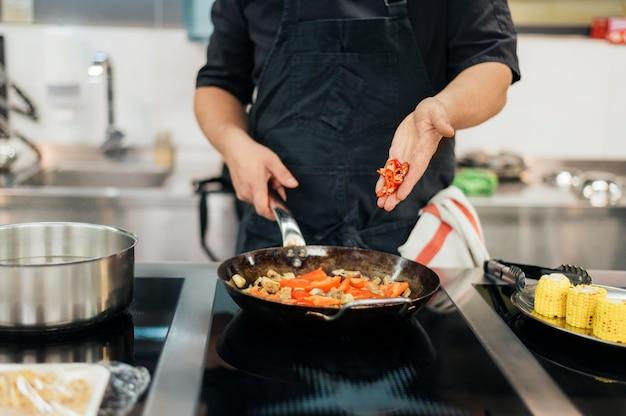 Шеф-повар-мужчина добавляет перец чили в блюдо