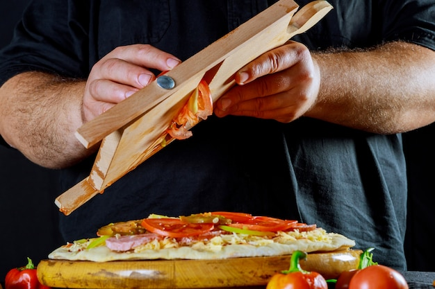 Male chef adding sliced tomatoes onto uncooked pizza