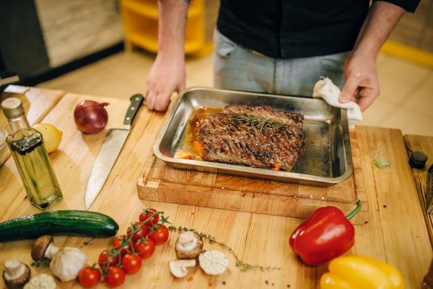 Повар-мужчина на сковороде с жареным мясом и овощами
