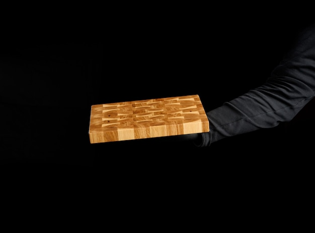 Male chef black clothes stands against a black background and holds in his hand a empty rectangular wooden kitchen chopping board, close up