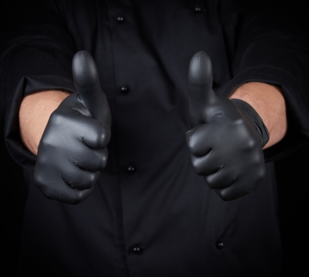 Male chef in black uniform shows a gesture of approval