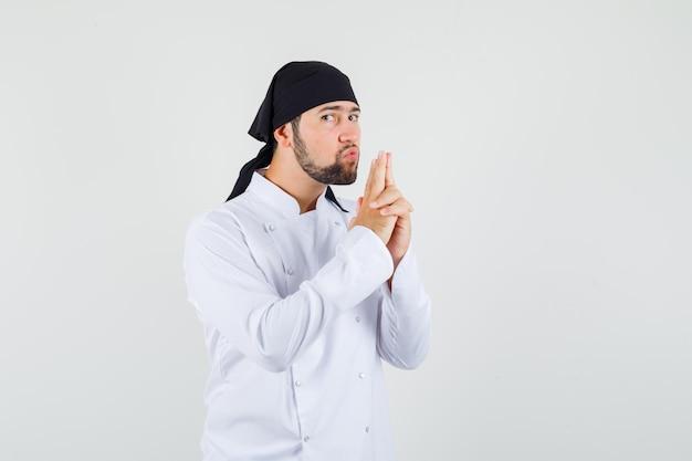 Cuoco unico maschio che soffia sulla pistola fatta dalle sue mani in uniforme bianca e sembra fiducioso. vista frontale.
