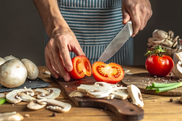 A male chef in a blue apron is cutting appetizing fresh tomatoes with a knife to prepare a dish. concept of the cooking process.