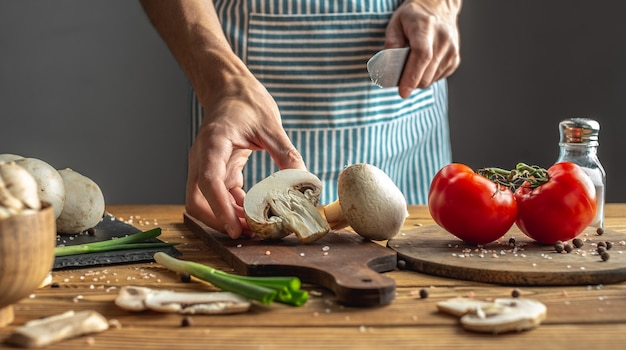 A male chef in a blue apron is cutting fresh mushrooms with a knife. concept of process of cooking a delicious dish.