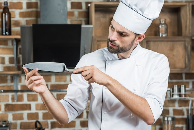 Male chef checking sharpness of knife