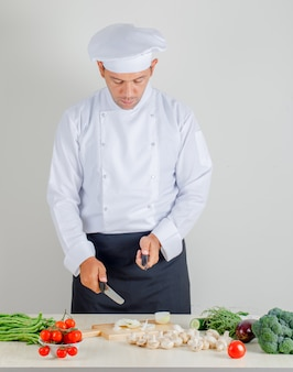 Male chef choosing knife for chopping onion in kitchen in uniform, hat and apron