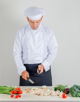 Cuoco unico maschio che sceglie coltello per tagliare cipolla a pezzi in cucina in uniforme, cappello e grembiule