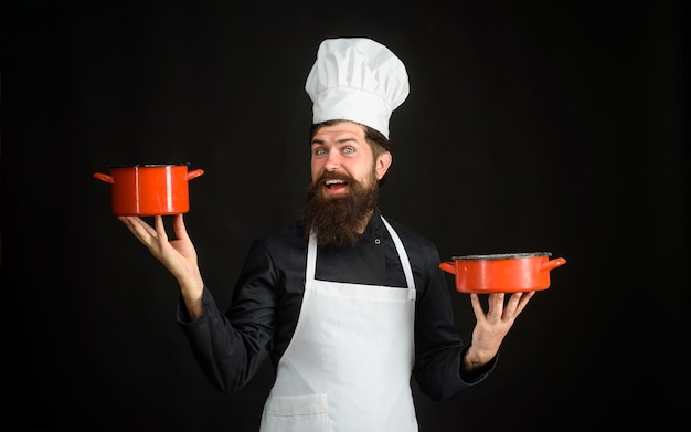 Male chef cook baker in uniform holds saucepan in hands chief man in white apron with pots bearded