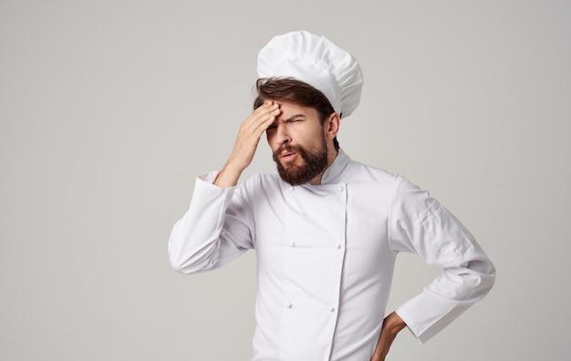 男性シェフのクックは、キッチンでの感情レストランのプロの仕事をキャップします。