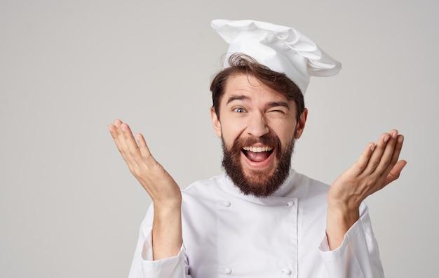 Шеф-повар-мужчина повар шапки эмоций ресторан профессионально работает на кухне.
