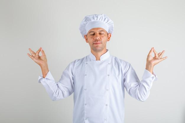 Cuoco maschio del cuoco unico che fa gesto di meditazione con gli occhi chiusi in uniforme e cappello