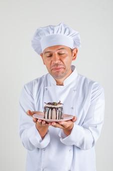 男性シェフがユニフォームと帽子で目を閉じてケーキを保持