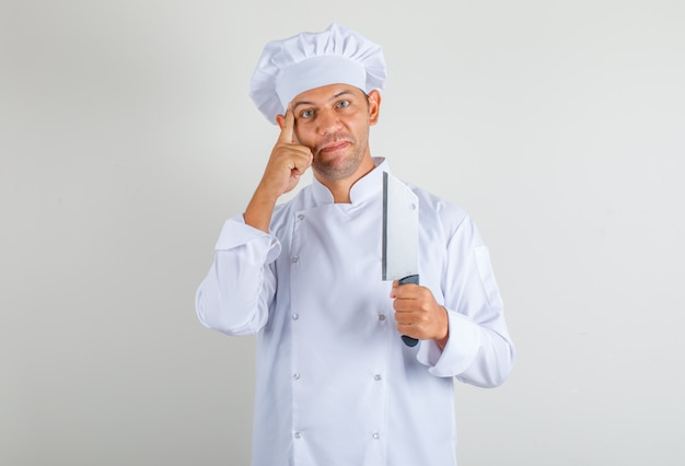 Мужской шеф-повар держит нож для мяса и думает в форме и шляпе и смотрит позитивно