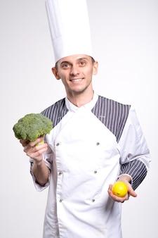 남성 요리사는 흰 벽 스튜디오 초상화에 고립 된 흰색 유니폼 셔츠 포즈에서 남자를 요리합니다. 요리 음식 개념. 복사 공간을 모의합니다. 브로콜리와 흰색에 요리사 클로즈업의 손에 레몬