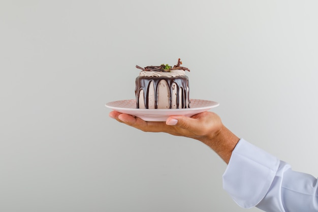 Male chef cook in uniform holding dessert cake in plate