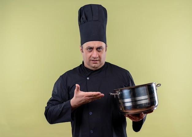 男性シェフの料理人は黒い制服を着て、緑の背景の上に立って混乱しているように見える腕を持つ鍋を示す帽子を調理します
