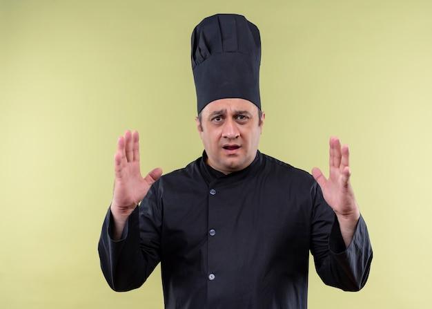 男性シェフの料理人は黒い制服を着て、大きなサイズのサインを示す手で身振りで示す帽子を調理し、驚いて、緑の背景の上に立っているシンボルを測定します