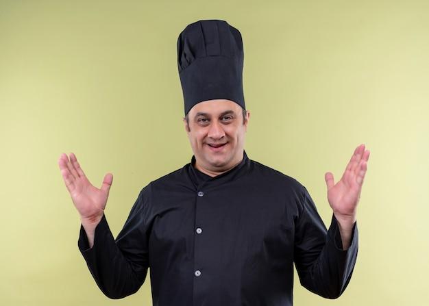 男性シェフの料理人は黒い制服を着て、緑の背景の上に立っている腕を上げてカメラで幸せで前向きな帽子を調理します