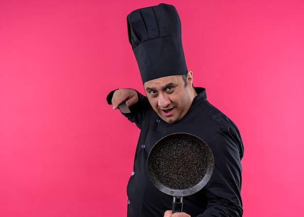 남성 요리사는 검은 색 유니폼을 입고 요리사 모자를 들고 분홍색 배경 위에 서있는 심각한 얼굴로 카메라를보고 팬과 칼을 들고 요리합니다.