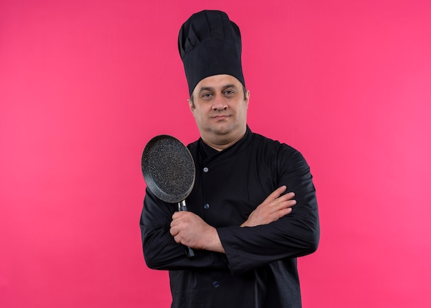 ピンクの背景の上に立っている自信を持って表情でカメラを見て鍋を保持している黒い制服と料理の帽子を身に着けている男性シェフの料理人