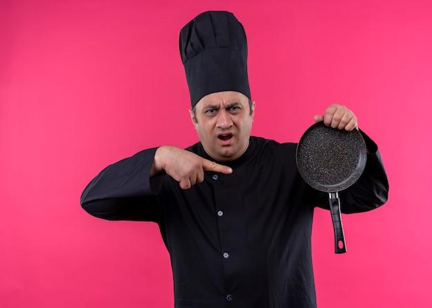 男性シェフの料理人は黒い制服を着て、ピンクの背景の上に立って積極的な表情で叫んで、それを指で指している鍋を持って帽子を調理します