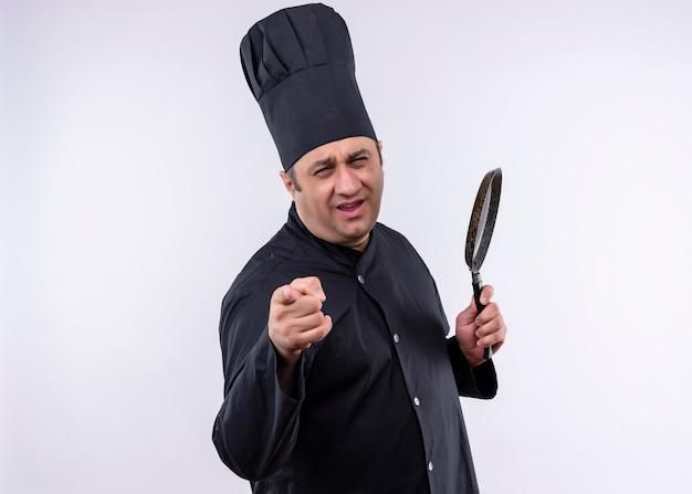 男性シェフは、黒い制服を着て、白い背景の上に幸せで前向きに立ってカメラに指で指している鍋を持って帽子を調理します
