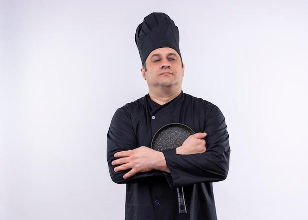 黒の制服を着て、白い背景の上に立っている目を閉じて鍋を持って帽子を調理する男性シェフ