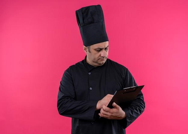 黒の制服を着た男性シェフの料理人とピンクの背景の上に立っている真面目な顔でクリップボードを保持している帽子を調理