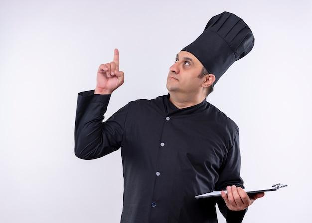 男性シェフは、黒い制服を着て、白い背景の上に立って指でクリップボードのポインティングを保持している帽子を調理します