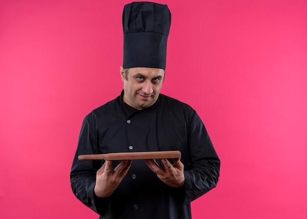 男性シェフの料理人は黒い制服を着て、ピンクの背景の上に立って自信を持って見えるカッティング木の板を保持している帽子を調理します