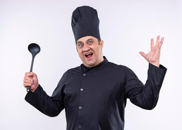 男性シェフの料理人は黒い制服を着て、白い背景の上に立っている積極的な表情でカメラを見て取鍋を上げる腕を保持している帽子を調理します