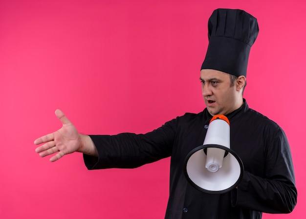 男性シェフの料理人は黒い制服を着て、ピンクの背景の上に立って質問をするために腕を出してメガホンを持って帽子を調理します
