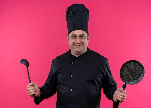 黒の制服を着て、ピンクの背景の上に立って自信を持って笑顔の鍋とおたまを持って帽子を調理する男性シェフ