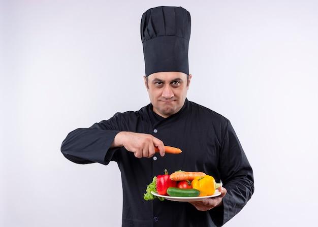 男性シェフは、白い背景の上に立っている真面目な顔でカメラを見て新鮮な野菜とニンジンとプレートを保持している黒い制服と料理人