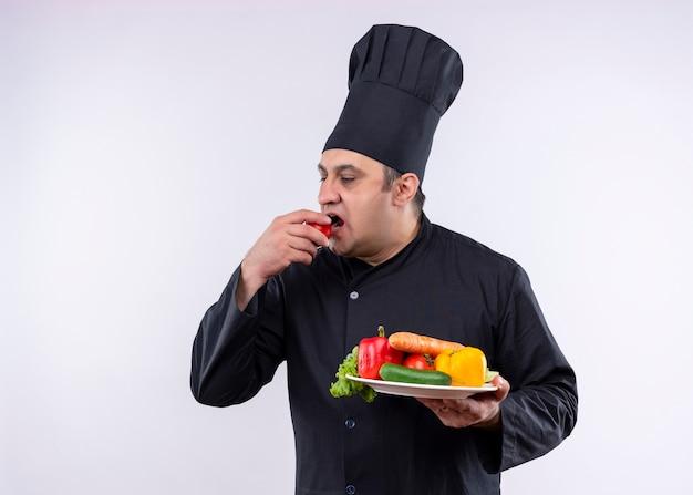 Шеф-повар-мужчина в черной униформе и поварской шляпе держит тарелку со свежими овощами, кусающими помидор, стоя на белом фоне