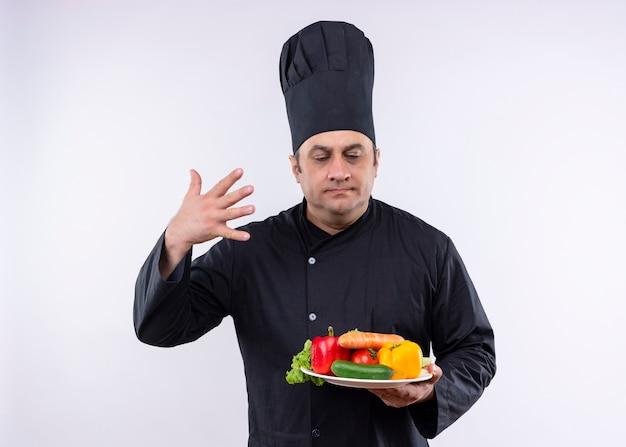 Шеф-повар-мужчина в черной униформе и поварской шляпе держит тарелку со свежими овощами, вдыхая аромат свежих овощей, стоящих на белом фоне