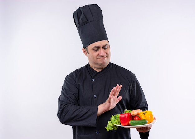 Шеф-повар-мужчина в черной униформе и поварской шляпе держит тарелку со свежими овощами, делая защитный жест со скептическим выражением лица, стоя на белом фоне