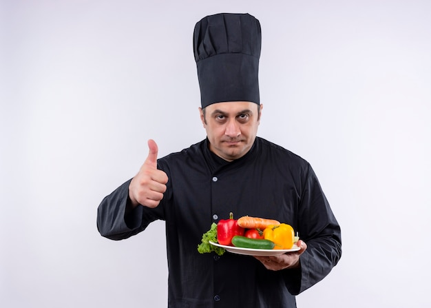 남성 요리사는 검은 색 유니폼을 입고 요리하고 흰색 배경 위에 서있는 엄지 손가락을 보여주는 신선한 야채와 함께 접시를 들고 모자를 요리
