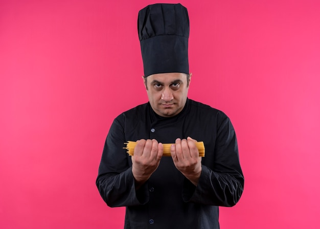 ピンクの背景の上に立っている真面目な顔でカメラを見て生のスパゲッティを保持している黒い制服と料理人の帽子を身に着けている男性シェフの料理人