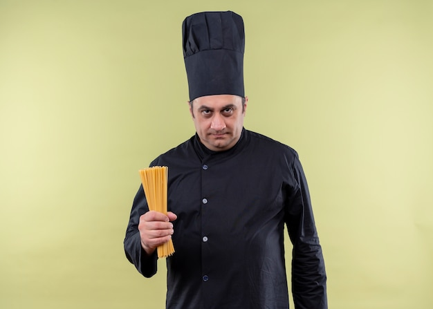 黒の制服を着て、緑の背景の上に立っている真面目な顔でカメラを見て列スパゲッティを保持している帽子を調理する男性シェフ