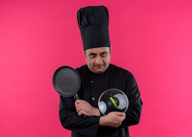 黒い制服を着た男性シェフの料理人とピンクの背景の上に立っている深刻な顔でカメラを見て手を交差させる鍋を持って帽子を調理します
