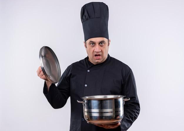 男性シェフの料理人は黒い制服を着て、白い背景の上に立って混乱しているカメラを見て鍋を持って帽子を調理します