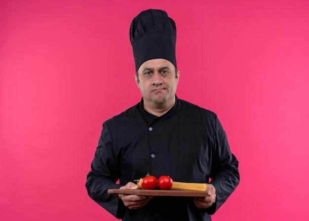 ピンクの背景の上に立っている真面目な顔でカメラを見てトマトと木製のまな板を保持している黒い制服と料理人のシェフの料理人