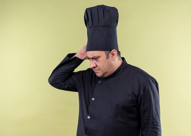 男性シェフの料理人は黒い制服を着て、混乱して脇を見て帽子を調理し、緑の背景の上に立っている何かを忘れました