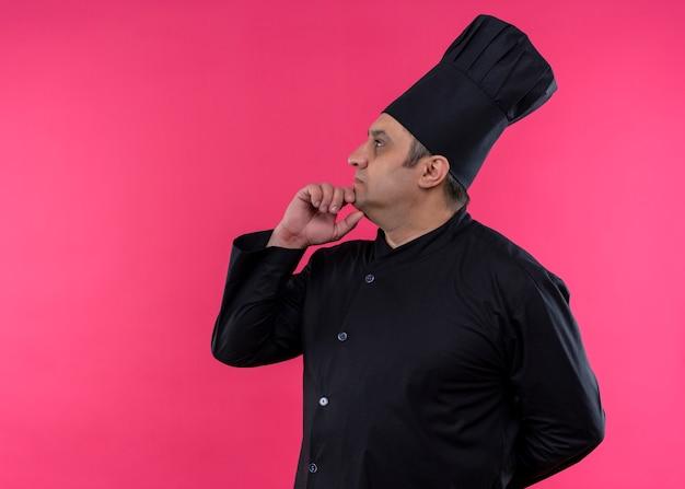 ピンクの背景の上に立っている物思いにふける表情で顎に手を脇に見ている黒い制服と料理人の帽子を身に着けている男性シェフ