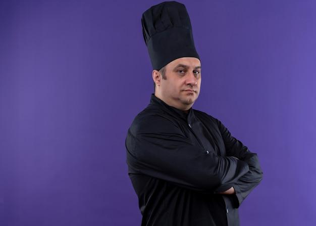 남성 요리사는 검은 색 유니폼을 입고 요리사 모자를 보라색 배경 위에 서있는 가슴에 교차 팔로 자신감 표정으로 카메라를보고 요리합니다.
