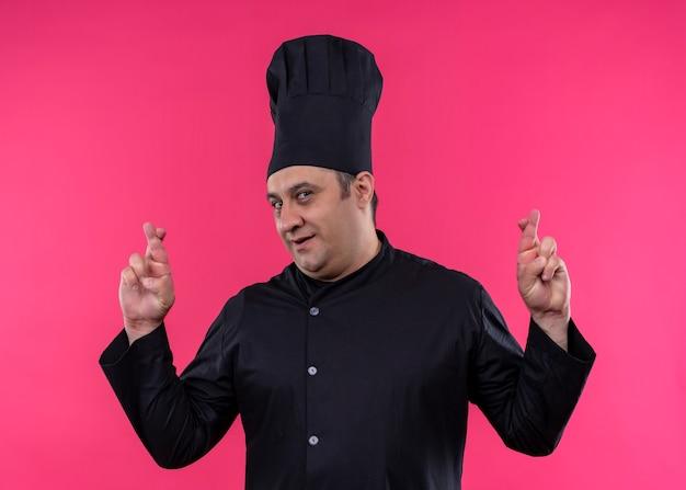 男性シェフは、ピンクの背景の上に立っている指を交差させる望ましい願いを作る黒い制服と帽子を身に着けている料理人