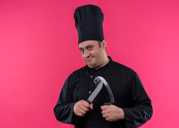 男性シェフは黒い制服を着て料理人とピンクの背景の上に立っている深刻な顔でカメラを見て帽子研ぎナイフを調理します