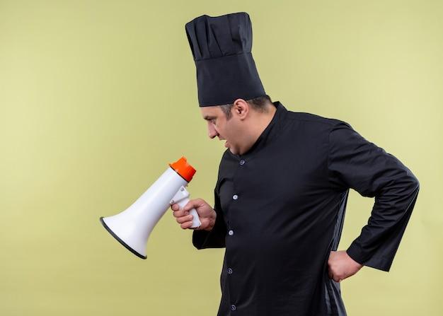 Шеф-повар-повар в черной униформе и в шляпе повара кричит в мегафон, стоя на зеленом фоне