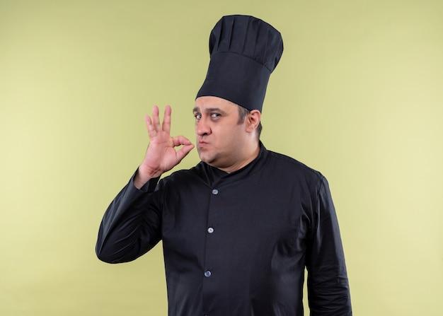 黒の制服を着て、緑の背景の上においしい立っているための兆候を示す帽子を調理する男性シェフ
